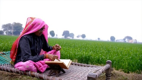 A medium shot of an aged woman of a village reading a holy book near a farmland