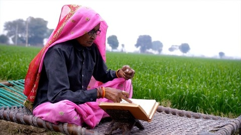 An aged woman of a village worshipping God by reading a religious book