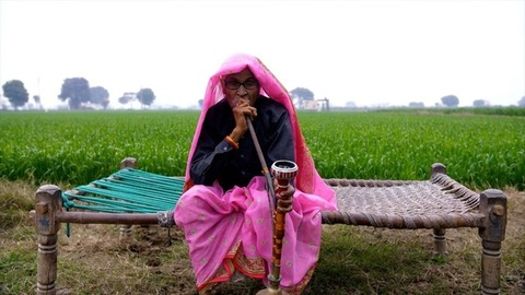 Medium shot of a woman smoking a hookah while sitting comfortably on a chaarpai