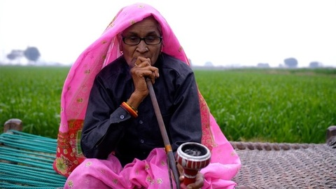 A medium shot of an elderly lady spending her free time smoking Indian pipe