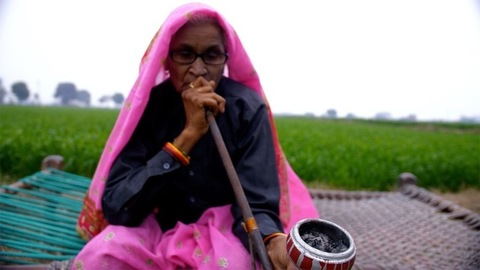 A medium shot of an old Indian woman, relaxing while having hookah in free time