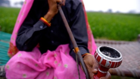 A close-up shot of an old lady smoking an Indian traditional pipe (hookah)
