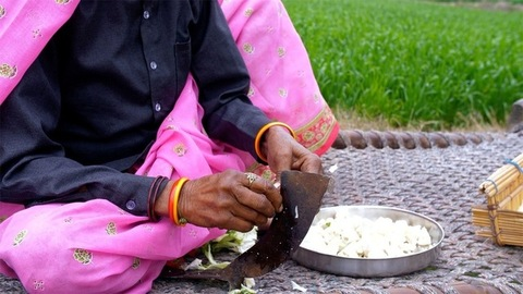 Close up shot of a woman's hand cutting vegetables using an Indian knife