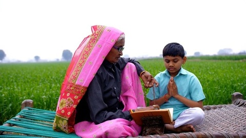 A little village boy sitting with his old grandmother while she worships God