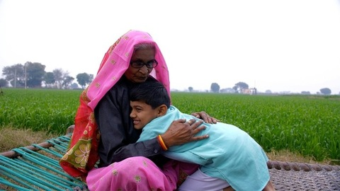 A little village boy near green farmland, happily hugging his grandmother