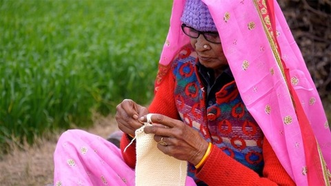 An old woman knitting sweater for her loved ones sitting near a farmland
