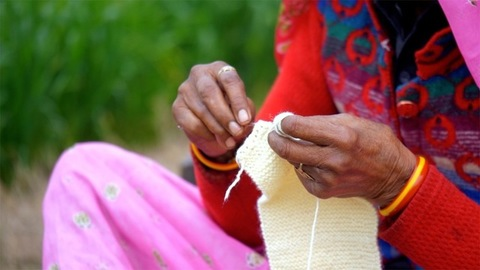 Closeup shot of an old village woman's hand knitting a sweater for her loved ones
