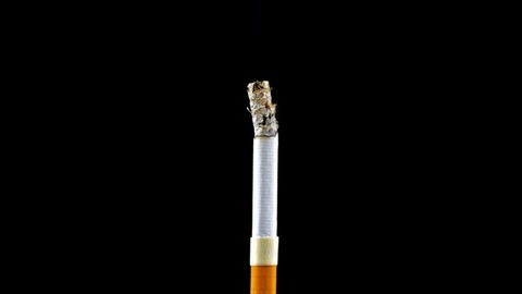 Time-lapse shot of a standing toxic cigarette burning out against a dark background
