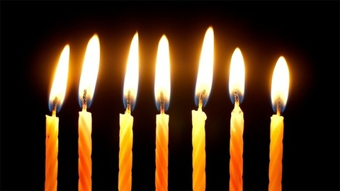 A set of birthday candles burning brightly against a black background