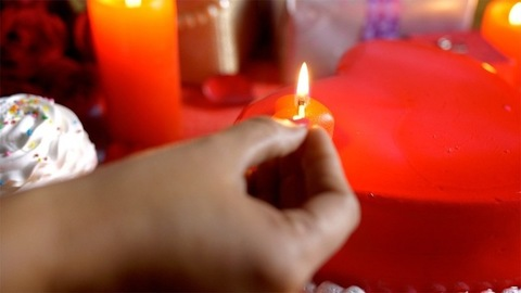 Indian woman lighting a red candle with a match for Valentine's day celebration in India