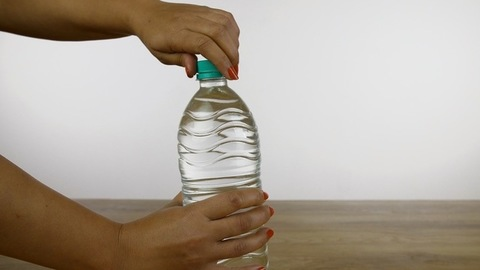 Woman hands placing a water bottle on a wooden platform and opening the cap