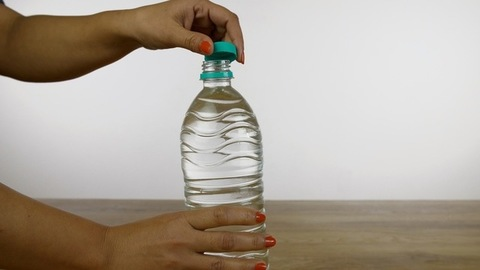 Closeup of woman hands closes the cap of a plastic bottle filled with freshwater