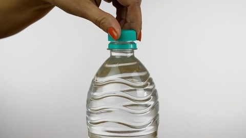 Slow-motion shot of a cropped Indian female closing a bottle of mineral water