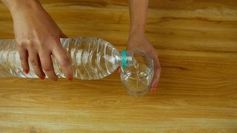 High angle shot of woman hands pouring freshwater from a bottle into a glass