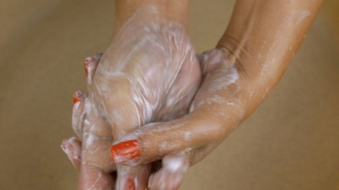 High angle shot - Indian woman lathering hands with white soap before washing