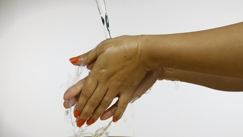 Closeup shot of a cropped Indian woman washing her hands with running water