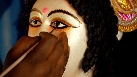 Hands of an Indian artist drawing eyes of the Goddess Durga's clay sculpture