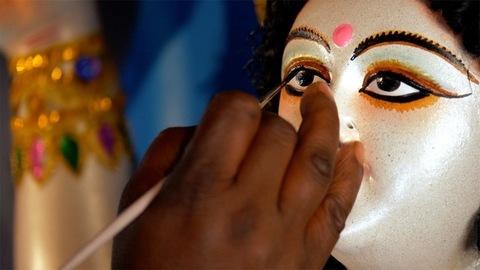 Closeup shot of an Indian craftsman drawing the eyes of Goddess Durga's statue