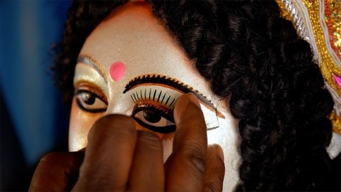 Hands of an Indian artist the painting eyelashes of Goddess Durga's sculpture