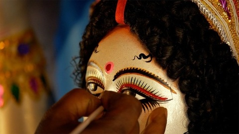 Closeup shot of a craftsman's hand painting the eyes of Ma Durga's sculpture