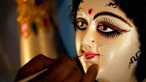 Hands of an Indian artist coloring the lips of clay sculpture of Goddess Durga