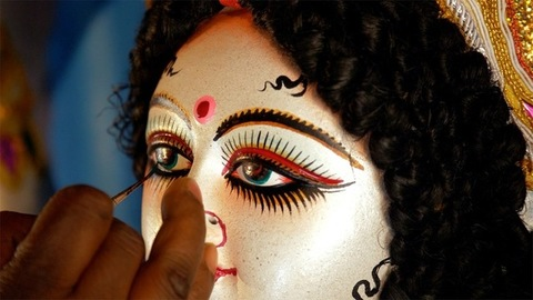 A craftsman giving finishing touches to the eyes of Goddess Durga's sculpture
