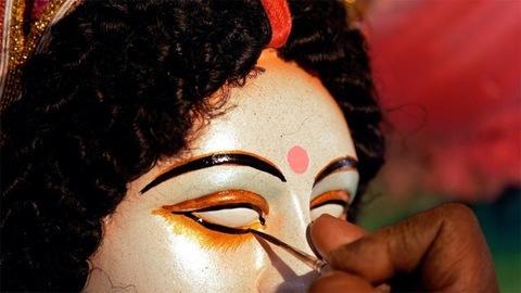 Closeup shot of an Indian artist drawing eyes of Goddess Durga's clay sculpture