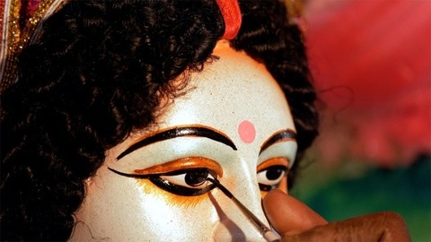 Hands of an Indian painter drawing eyes of the Hindu idol Ma Durga's statue