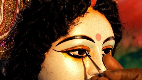 A craftsman's hand painting the eyes of a clay statue of Hindu idol Ma Durga