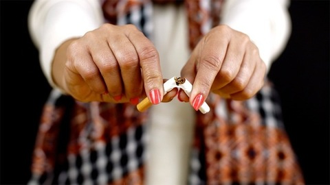 Female breaking a cigarette - quit smoking concept