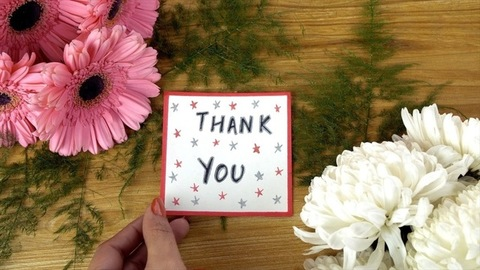 Woman hands placing a greeting card with 'Thank you' text on a decorated surface