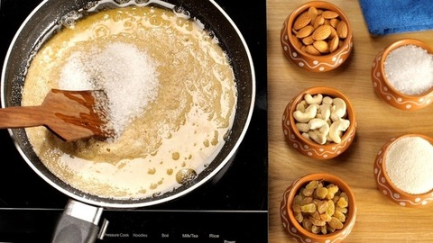 Female's hand mixing white refined sugar with Sooji/Suji/semolina Halwa/pudding