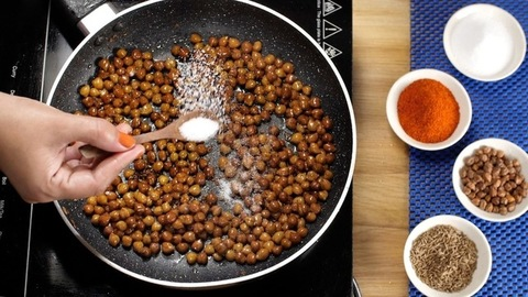 Lady's hand sprinkling salt in the boiling Chana Masala gravy cooking in a frying pan