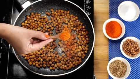 Preparation of popular Indian small black chickpea spicy fry in a home kitchen