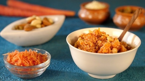 Dry fruits dropping in a bowl with grated carrots and carrot pudding on a table