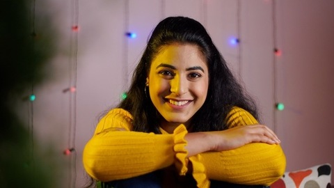 Attractive young Indian lady smiling while sitting in her home during the festive time