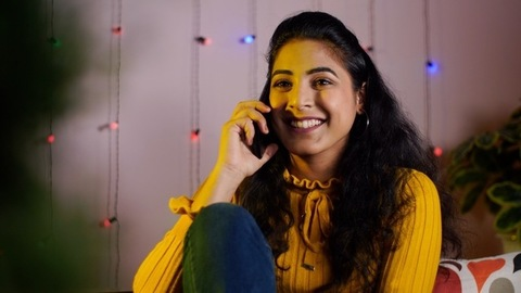 Young modern Indian female in winter dress cheerfully talking on the phone - happy moments