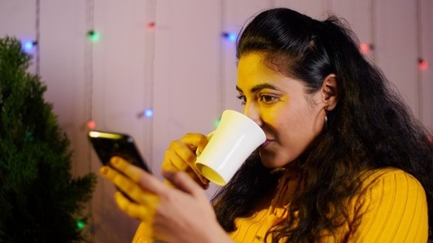 Portrait of a cheerful Indian girl browsing her smartphone while drinking tea / coffee