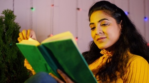 Portrait of young Indian girl reading a book while sitting in a decorated room