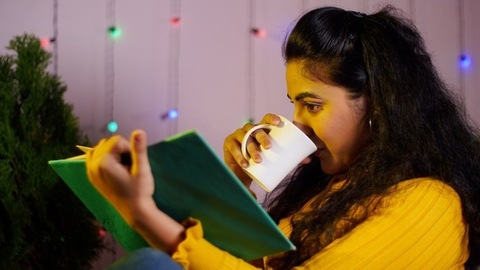 Portrait of a young woman reading a book while drinking tea / coffee in the morning