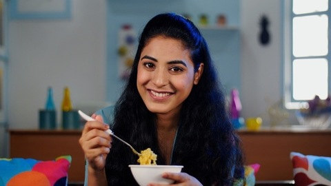 Smiling woman in her early twenties eating a bowl of freshly made hot noodles