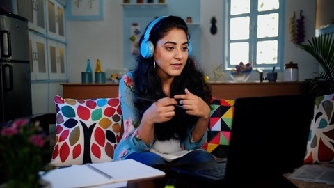 Indian female talking on a video call on the laptop and making her notes
