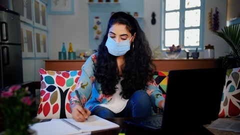 Indian female making notes of her online education wearing a medical mask