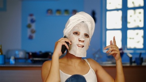 A young lady with a serum sheet mask on her face happily talking on a smartphone