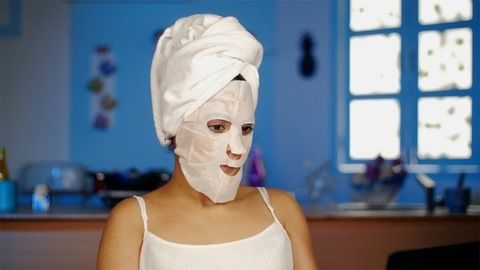 Indian female in white clothes relaxing at her home with a cosmetic face mask
