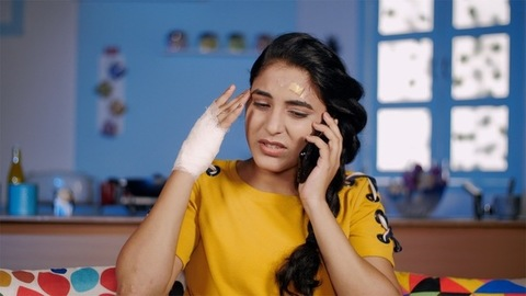 Beautiful Indian teenager talking on a smartphone after meeting with an accident