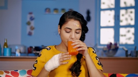 Injured young woman drinking healthy orange juice sitting at home to get fit