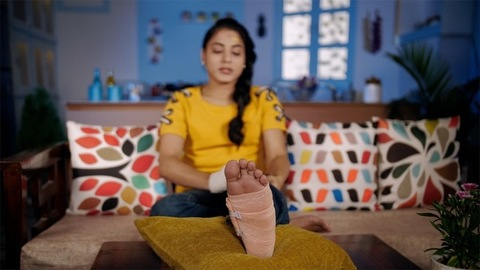 Indian teenager applying a crepe bandage on her legs and putting it on a soft cushion