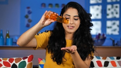 Indian pretty woman with perfect skin taking hair oil from the bottle - beauty concept