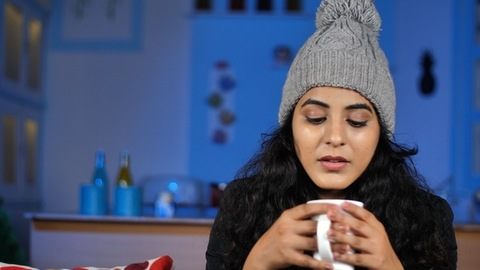 Pretty woman wearing cozy winter clothes blows and drinks a cup of tea / coffee